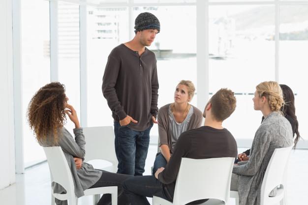 grupo-de-rehabilitacion-escuchando-al-hombre-de-pie-presentandose-a-si-mismo_13339-36863