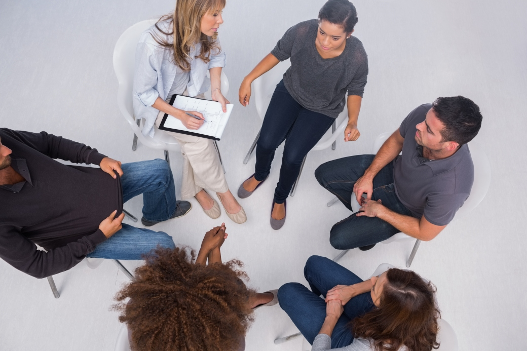 Patients listening to each other in group session sitting in circle
